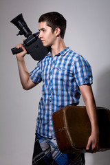 Young man filmmaker with old movie camera and a suitcase in his