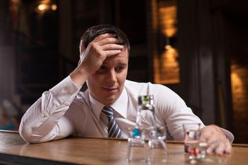Upset businessman having drink in bar.