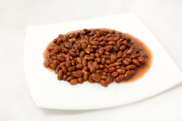 An overhead view of canned black beans on a white background