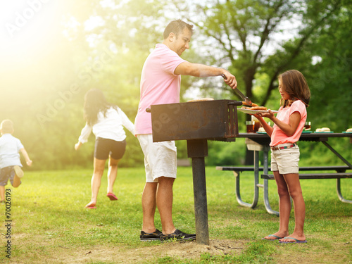 food getting served at family barbecue while children play - 70026193