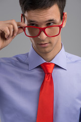 young man removing glasses on grey background.