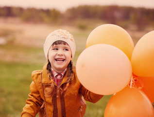 happy girl with orange balloons outdoor