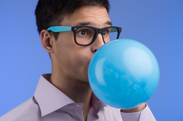 Man blowing up balloon on blue background.