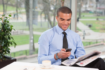 young handsome business man typing sms.