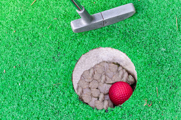Close-up Mini Golf hole with bat and ball