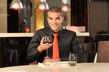 Elegant young man holding glass of red wine.