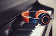 Blue-orange headphones on a digital piano keyboard - 70028301