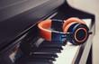 Leinwanddruck Bild - Blue-orange headphones on a digital piano keyboard