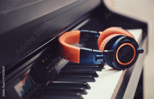 Leinwanddruck Bild Blue-orange headphones on a digital piano keyboard