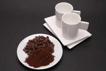 Plate with roasted coffee beans and ground coffee with two cups