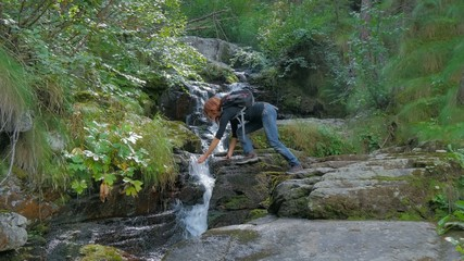 hiker woman drinking water from a torrent in a wild forest