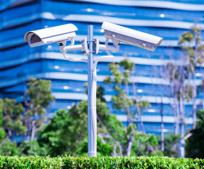 CCTV camera or surveillance operaiting with blue building and pa