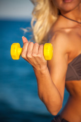 Sweaty fitness woman working out with dumbbells in summer on bea