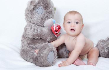Baby  sitting next to a teddy bear