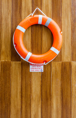 The orange life buoy hanging on the wood wall  for safety and re