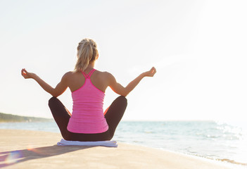 Silhouette of healthy woman practicing yoga on the beach