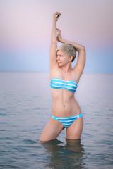 Девушка в море встречает рассвет