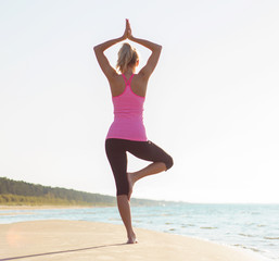 Silhouette of young healthy woman practicing yoga on the beach