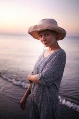 Девушка в шляпе на берегу моря на рассвете