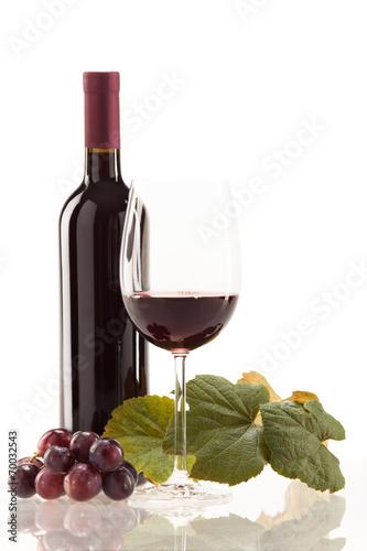 Foto op Aluminium Wijn Rotwein im Glas mit Frucht, Blätter und Weinflasche
