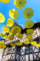 Green upside down umbrellas in a street, Thiers (France)