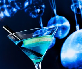 blue cocktail with sparkling disco balls background