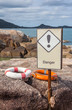 Two life buoys orange and white on the rock and danger sign near
