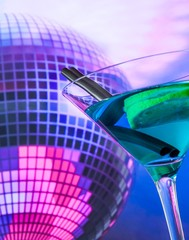 blue cocktail with sparkling disco ball background