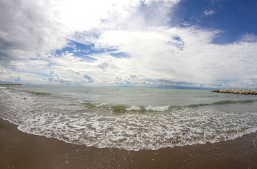 beach of the sea with clouds on the horizon with fisheye lens