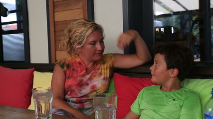 Mother and son sitting at cafe and talking
