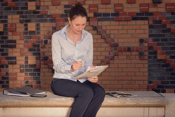 Junge Geschäftsfrau sitzt im Foyer und liest