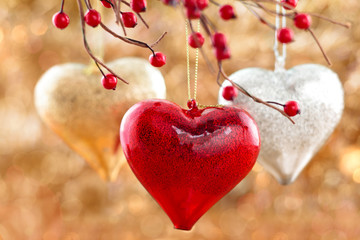 Three hearts hanging on tree against holiday lights.