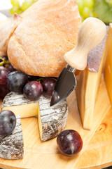 Käseplatte mit roten Weintrauben und Weissbrot