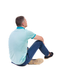 Back view of seated handsome man in polo looking up.