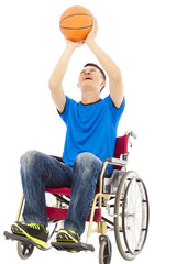 young man sitting on a wheelchair and holding a basketball