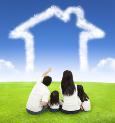 happy family sitting on a meadow with house of clouds