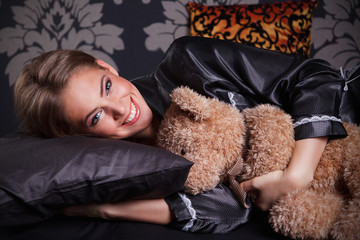 Beautiful young woman hugging a teddy bear in the bed