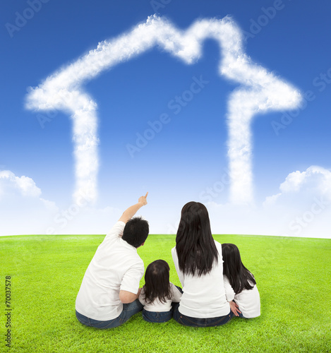 canvas print picture happy family sitting on a meadow with house of clouds