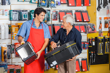Man Looking At Salesman While Selecting Toolbox