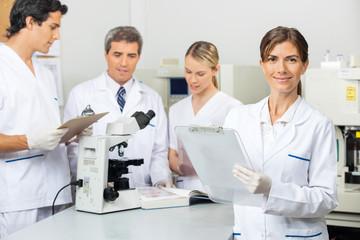 Female Scientist Holding Clipboard In Laboratory