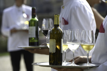 Waiters are serving vine at a wedding outdoor party
