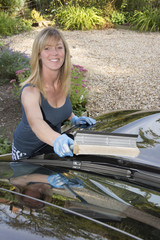 Female motorist cleaning car windscreen
