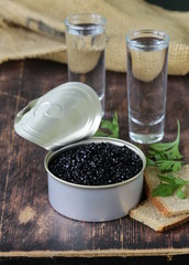 caviar with rye bread and two shots vodka on a wooden table