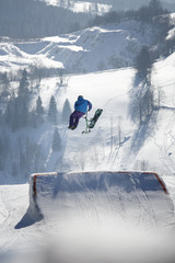 Young man jumps on his snow bike in snow park.