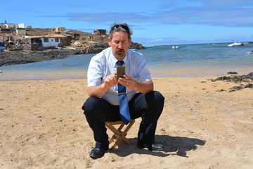 Business man in suit on the beach calling by mobile phone