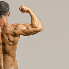 Bodybuilder showing his back and biceps muscles, fitness trainer