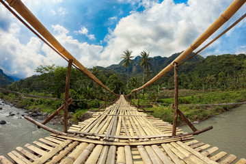 Suspension bamboo bridge across the river in a forest and rice f