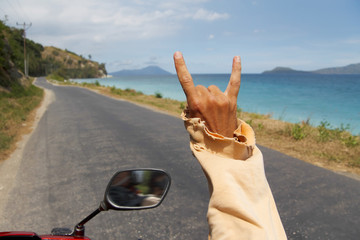 Guy driving motorbike along amazing tropical road and seaside an