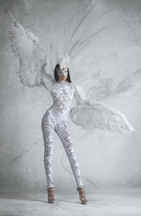 Woman in white angel costume with wings