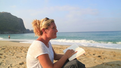 Woman sitting on the beach and reading a book